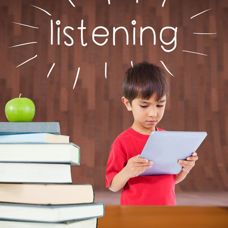 The word listening and cute boy using tablet against red apple on pile of books photo