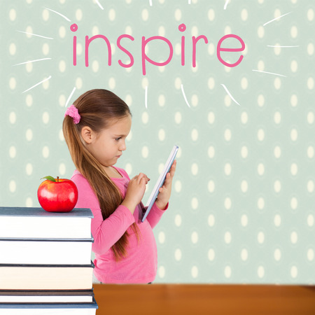 The word inspire and cute girl using tablet against red apple on pile of books photo