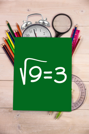 square root: Square root of three against students desk with green page
