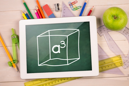 cubed: Composite image of digital tablet on students desk a cubed