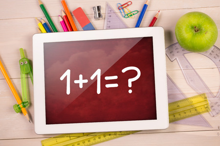 Composite image of digital tablet on students desk showing math equations photo