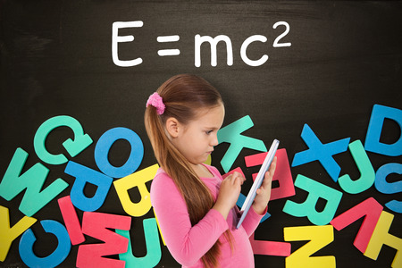 jumbled: Cute girl using tablet against alphabet magnets in a jumble on blackboard Stock Photo