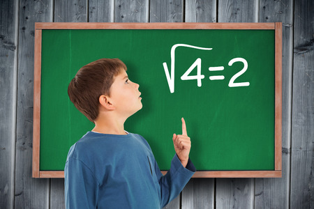 square root: Cute boy pointing against blackboard on wooden board
