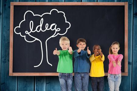 Cute kids showing thumbs up against blackboard on wooden board photo