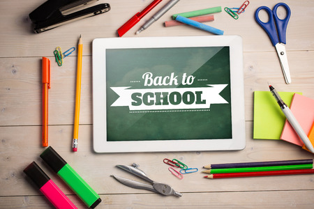 escuela primaria: Imagen compuesta de tableta digital en estudiantes de escritorio que muestra el mensaje de vuelta a la escuela