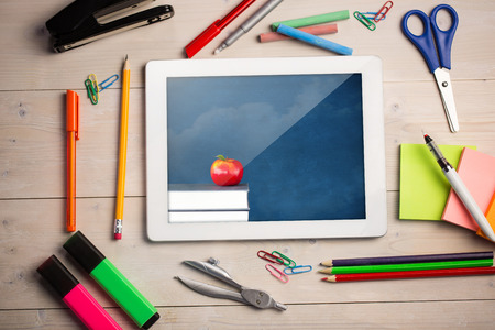 Composite image of digital tablet on students desk showing apple on books