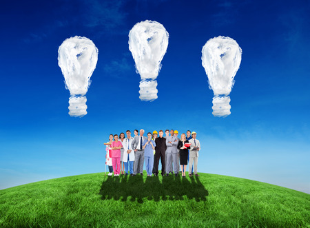 Smiling group of people with different jobs  against cloud light bulbs photo
