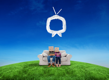 Silly employees with arms folded wearing boxes on their heads against cloud tv photo