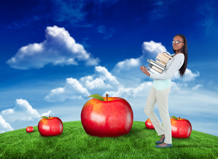 medium size: Side view of young woman carrying a pile of books against green field under blue sky Stock Photo