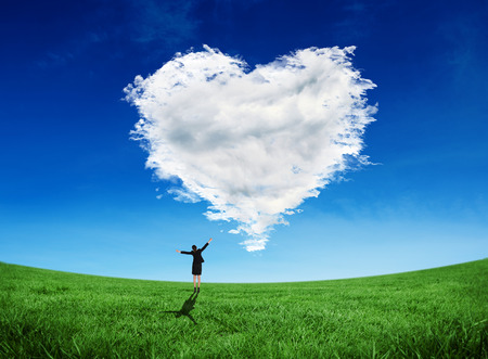 Composite image of excited businesswoman cheering against cloud heart