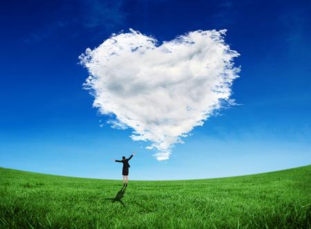Image composite de femme d'affaires heureux acclamations contre coeur de nuage