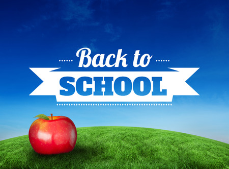 Red apple with back to school message against green hill under blue sky photo