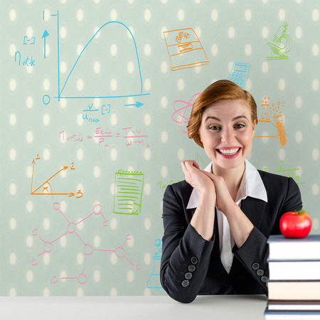 Excited redhead teacher sitting at desk against red apple on pile of books photo