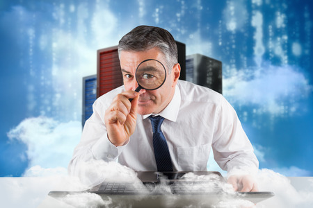 Mature businessman examining with magnifying glass against cityscape on cloud photo