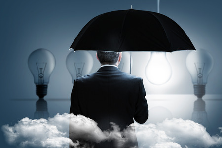 Mature businessman holding an umbrella against five light bulbs in a row with one lit up photo