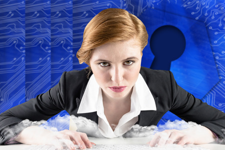 Redhead businesswoman sitting at desk typing against keyhole graphic on blue background photo