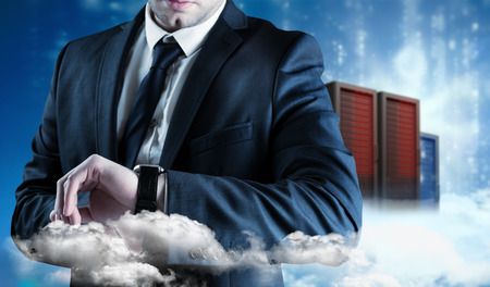 Businessman checking the time on watch against cityscape on cloud photo