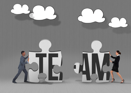 The word team and businessman pushing against grey jigsaw pieces photo
