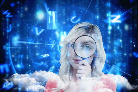 Fair-haired woman looking through a magnifying glass against lines of blue blurred letters falling photo
