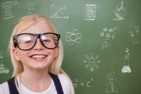 Cute pupil smiling against school doodles photo