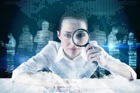Businesswoman typing and looking through magnifying glass against white silhouettes on black background photo