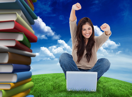 Woman looks straight ahead as she celebrates in front of her laptop against green field under blue sky photo