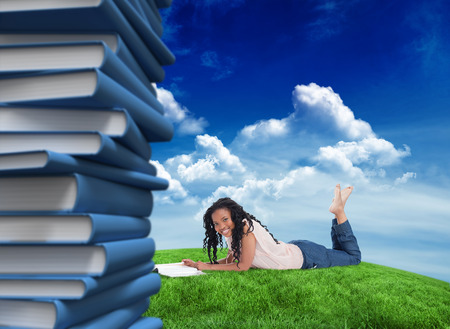 A woman lying on the floor smiling at the camera with a magazine in front of her against green field under blue sky photo
