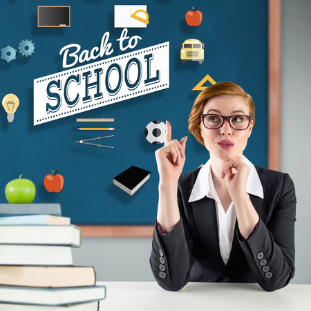 Thinking redhead teacher against green apple on pile of books in classroom photo