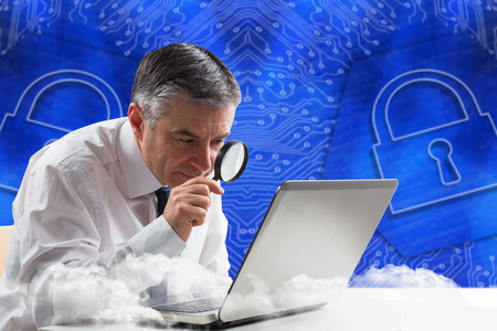 Mature businessman examining with magnifying glass against lock graphic on blue background photo