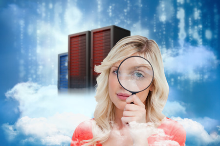 Fair-haired woman looking through a magnifying glass against cityscape on cloud photo