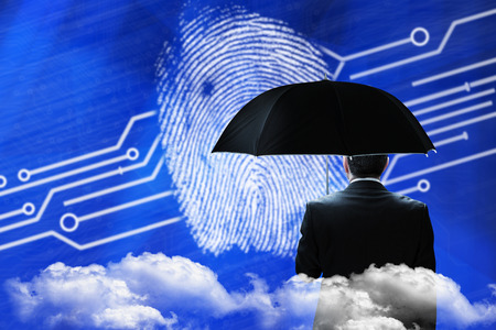 Mature businessman holding an umbrella against fingerprint on digital blue background photo