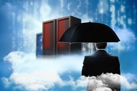 Mature businessman holding an umbrella against cityscape on cloud