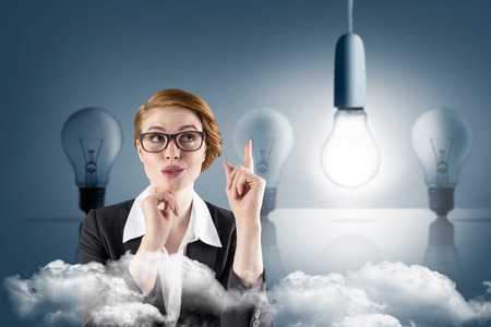 Thinking redhead businesswoman against five light bulbs in a row with one lit up photo