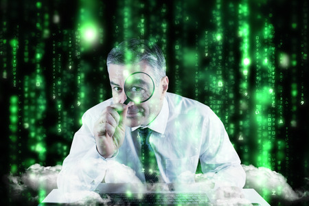 Mature businessman examining with magnifying glass against lines of green blurred letters falling photo