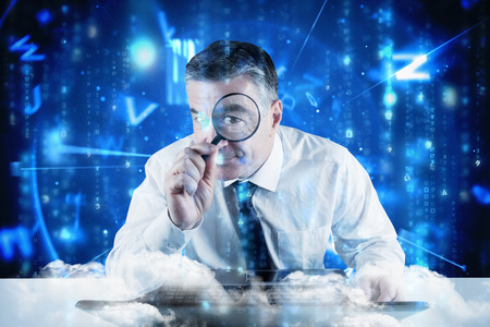 Mature businessman examining with magnifying glass against lines of blue blurred letters falling photo