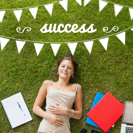 The word success and bunting against pretty student lying on grass photo