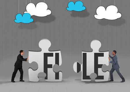 The word file and businessman standing and pushing against grey jigsaw pieces photo