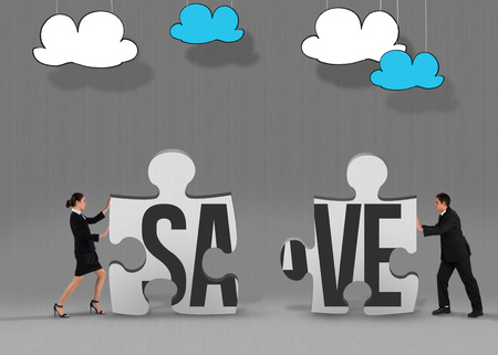 The word save and businesswoman pushing against grey jigsaw pieces photo