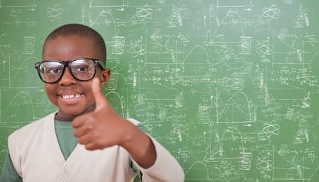 niños negros: Alumnos que muestran los pulgares para arriba contra lindas doodles de matemáticas y ciencias Foto de archivo