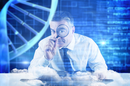 Mature businessman examining with magnifying glass against blue dna helix with texture photo
