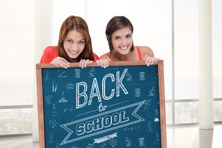 Teenage girls smiling while holding a blank poster and hiding behind it against blackboard with copy space on wooden board photo
