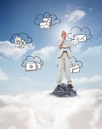 Thinking businessman against mountain peak through the clouds photo