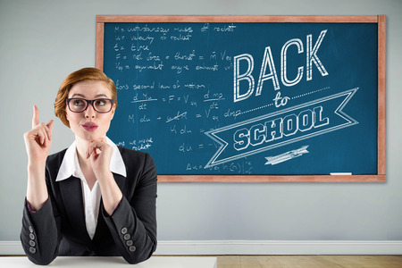 Thinking redhead businesswoman against blackboard with copy space on wooden board photo