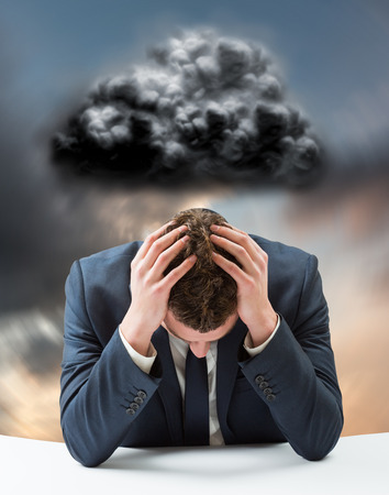 bowed head: Businessman with head in hands against blue and orange sky with clouds