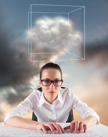 Businesswoman typing on a keyboard against blue and orange sky with clouds photo