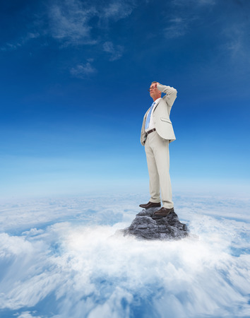Thinking businessman against mountain peak through the clouds photo