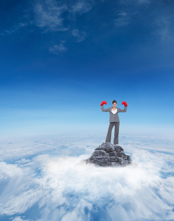 Businesswoman with boxing gloves against mountain peak through the clouds Stock Photo - 30864463