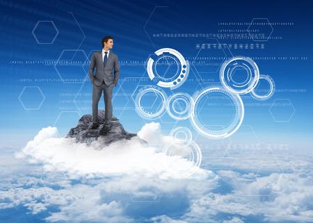 Handsome businessman against mountain peak through the clouds photo