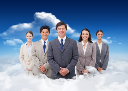 Smiling salesteam standing against bright blue sky with clouds photo