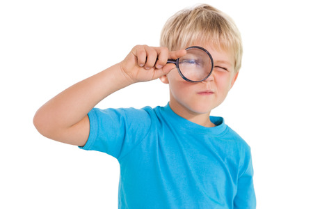 inquiring: Cute little boy looking through magnifying glass on white background